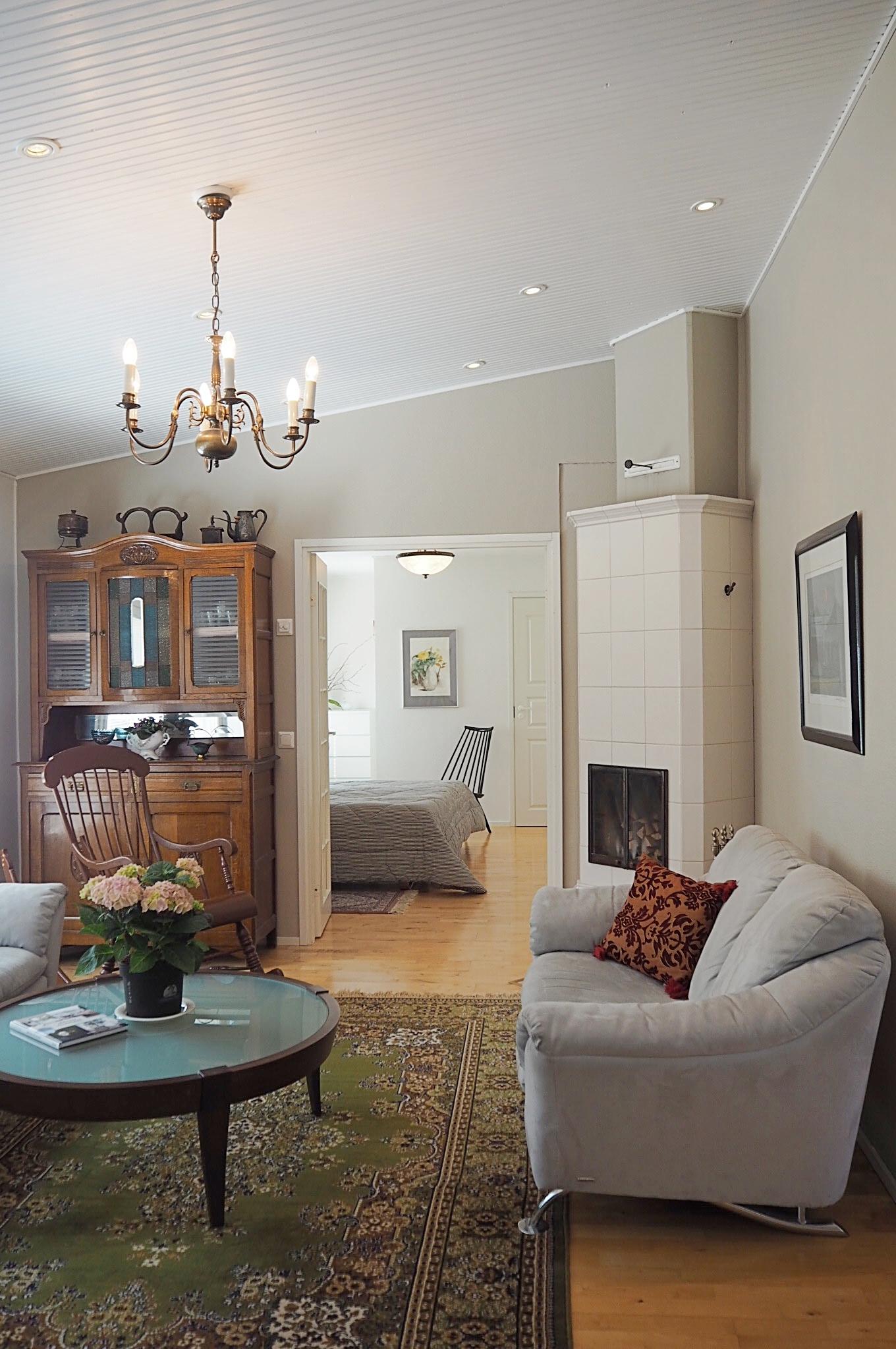 Viisto sisäkatto tuo olohuoneeseen avaruutta. Valkoinen kaakelitakka on varaava.