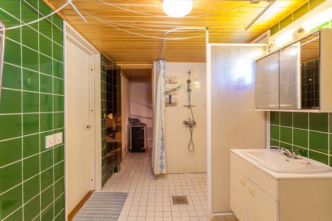 Tilava kylpyhuone, johon eteisestä ja takkahuone...