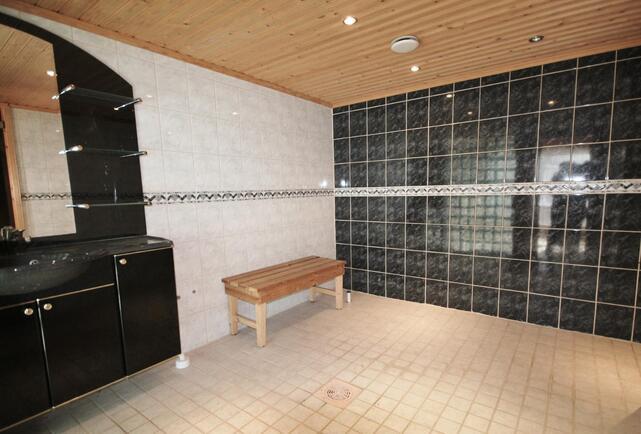 Tyylikkääksi ja reilun kokoiseksi rakennettu pesuhuone houkuttelee kylpemään