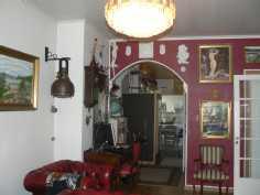 Olohuoneen punainen seinä, takana kylpyhuone ja pidemmällä keittiö
