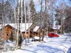 Päärakennus ja saunarakennus talvella pihalta