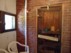 Pukuhuone ja sauna. Puukiuas ja suihku.Käynti kuistilta.