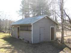 Talousrakennus, jossa puuvarasto, pukuhuone, pesuhuone, sauna ja puucee.