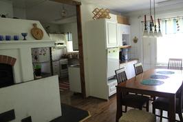 Keittiö ja ruokailuhuone, jossa leivinuuni sekä puu- ja sähköhellat
