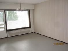 Olohuone-mistä kulku lasitetulle parvekkeelle ja näkymä taloyhtiön etelään avautuvalle pihamaalle