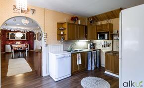 Kaksiosainen keittiö jatkuu seinän takana ja päättyy ruokailutilaan