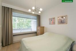 Isoimpaan makuuhuoneeseen johdattaa pariovet. Ikkuna parvekkeen suuntaan.