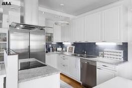 Tyylikäs ja vaaleasävyinen keittiö jossa on reilusti kaappi- ja laskutilaa.
