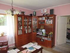 Kuvassa olohuone, johon keittiön isosta lämmitysmuuristosta tulee ...