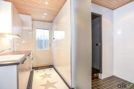 Kodinhoitohuoneesta avautuu lasiovet kylpyhuoneeseen.