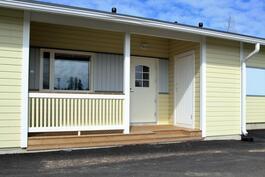 Sisäänkäynti suojassa aurinkoisella terassilla. Vasemmalla MH:n ikkuna. Oikealla ovi varastoon.
