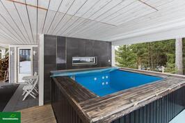 Saunarakennuksen terassilla puilla lämpenevä poreallas