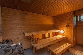 Saunassa on puu- ja sähkökiuas sekä pieni ikkunakin. Suihku on saunan sisällä.
