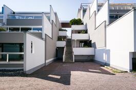 Ajattomat valkoiset amfitalot tarjoavat rivitalomaista asumista.
