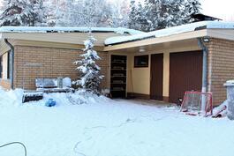 Sisäänkäynti suojassa katoksessa. Lisäksi ovet varastoon ja autotalliin.