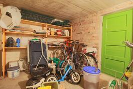 Kellarikerroksen varastohuone, vihreän oven takana kellari.