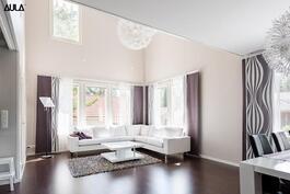 Korkeassa olohuoneessa on valoa ja ilmavuutta.