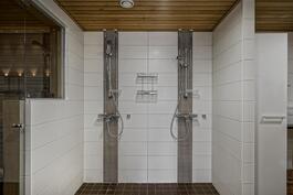 Kylpyhuoneessa kaksi suihkua. Vieressä myös kodinhoitosyvennys.