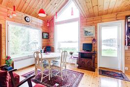 Saunarakennuksen ilmava olohuone ja isot ikkunat järvelle