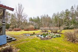 Etupihalla suihkulähde sekä kukkaan puhkeava puutarha