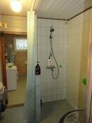 Kuvassa laatoitettu kylpyhuone, jossa ...