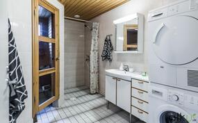 Kylpyhuoneessa on suihkutila verholla erotettu