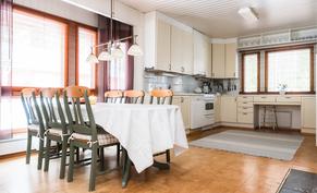 Vaalean sävyinen ja tilava erillinen keittiö..