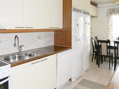 keittiössä täyskorkeat jääkaappi- ja pakastin ja ruokailutilan yläpuolella näppärät yläkaapit