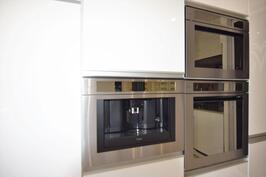 Keittiössä on integroitu kahvikone seinässä, uuni ja mikro.
