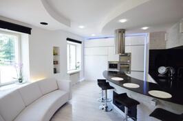 Olohuone yhdistyy hyvin varusteltuun mustavalkoiseen keittiöön.