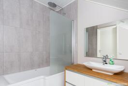 Yläkerran kylpyhuone on tilava ja harmooninen.