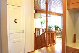 Eteisestä yläkerran kylpyhuoneen ovi, raput alakertaan ja olohuone