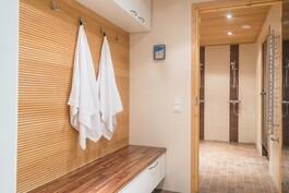 Tilava sauna pukuhuone, josta käynti pesuhuoneen kautta saunaan.