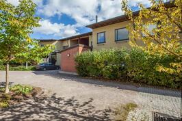 Myytävän huoneiston ulkovarasto, terassi pensasaidan takana ja julkisivu pihan puolelta.
