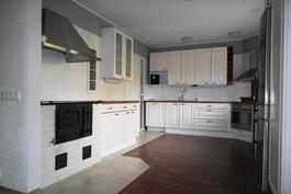 Isossa keittiössä runsaasti kaappeja sekä myös puuliesi