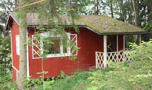 Pihan reunalla oleva puulämmitteinen saunarakennus.