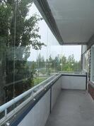 Lasitettu parveke on tilava ja suojaisa paikka istuskella lehtipuiden suojassa