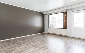 Olohuoneessa on tummanharmaaksi maalattu tehostepäätyseinä ja tyylikkäät laminaattilattiat.. .