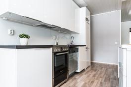 Keittiössä on eleettömän tyylikkäät valkeat korkeakiiltoiset kaapistot..