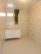 Pesuhuoneessa kodinhoitotila pesukoneliitäntöineen.