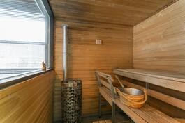 Sauna, jossa iso ikkuna, josta näkymät uima-altaalle ja pihalle