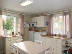 Keittiössä on runsaasti kaapistoja. Ikkunat kahdesta suunnasta tuovat mukavasti luonnon valoa