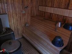 saunassa puulämmitteinen kiuas ja pata sekä juokseva vesi