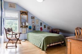 Yläkerran toisessa makuuhuoneessa ullakkoasumisen tunnelmaa.