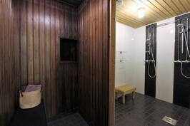 Saunaosaston pukuhuone, josta ikkuna löylyhuoneen kiukaalle päin, josta näkee onko kiukaassa tuli