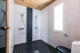Tilava kylpyhuone kahdella suihkulla