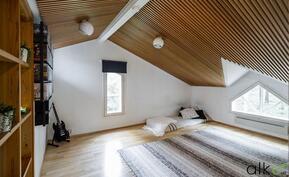 Kauniit ikkunat koristavat suurempaa makuuhuonetta.