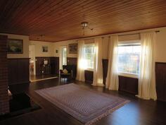 Yläkerran edustava tilava olohuone isolla varaavalla takalla.