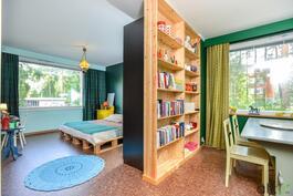 Olohuoneesta on eriytetty päämakuuhuone kirjahyllyllä ja kaapistoilla