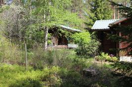 Päärakennus oikealla ja sauna jonka terassi on päivä ja iltapäiväaurinkoon.